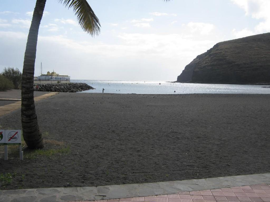 Рядышком с мариной пляж с черным песком.